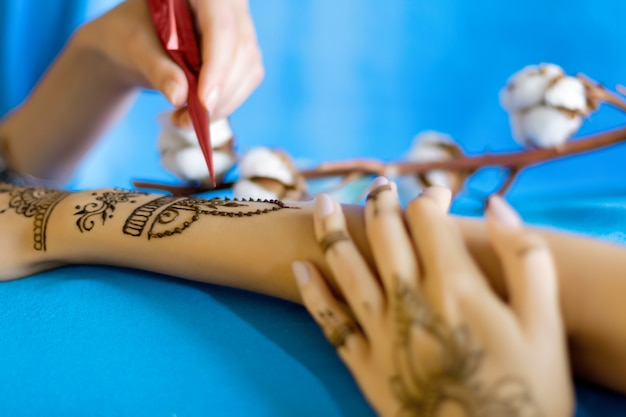 伝統的な東洋の一時的な刺青の飾りで描かれた女性の手首。インドの結婚式の準備、ヘナで女性の手をペイントするプロセス。ひだ、背景に綿の枝を持つ青い布。