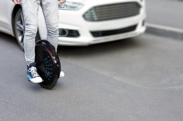 Будущее - теперь концепция. экологический транспорт. черный современный футуристический электрический одноколесный велосипед, одноколесный самокат или уравновешивающее электрическое колесо сравнивают с бензиновыми дизельными автомобилями. эко планета концепция