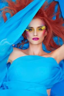 しょうがの髪と明るいときれいな女の子は柔らかい青と絹のような布で覆われて横になって作る