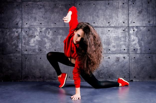 都市の壁の前で踊っている少女。