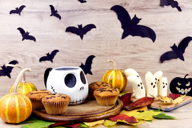 不気味なカップケーキ、カボチャ、葉、木製皿にコウモリのシルエット