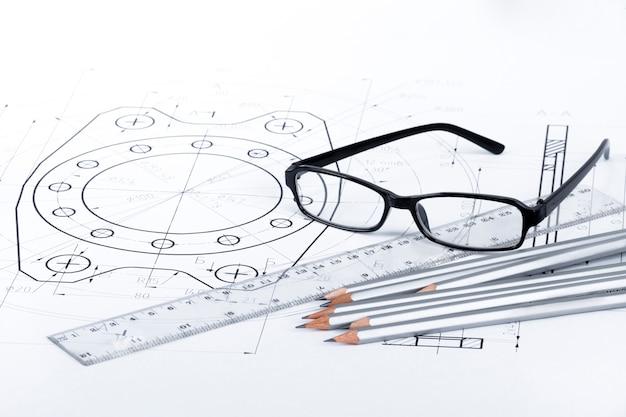 Калькулятор, очки, карандаш и линейка лежат на бумаге с механическими набросками турбины.