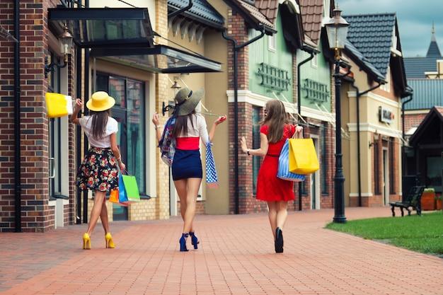 Довольно счастливые яркие женщины подруги в разноцветных платьях, шляпках и на высоких каблуках с сумками ходят по улице после покупок