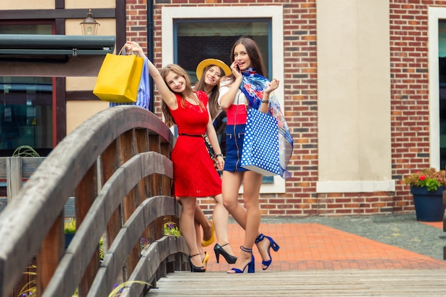 Довольно счастливые светлые женщины-девушки в ярких платьях и на высоких каблуках с сумками идут по улице после покупок