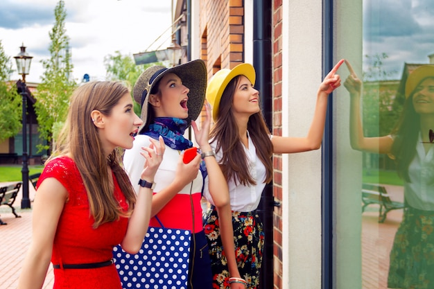 Удивленные яркие женщины подруги подруги в разноцветных платьях и шляпках в торговом центре ищут новую модную одежду в витрине магазина.