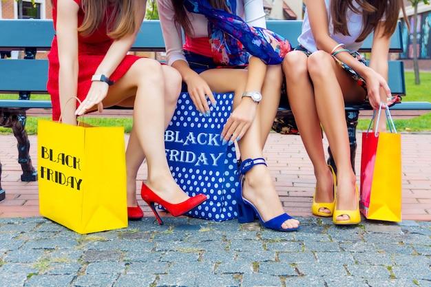 ショッピングモールで買い物をした後屋外に座ってカラフルなドレスで幸せなカラフルな女性女性大人女の子友達足