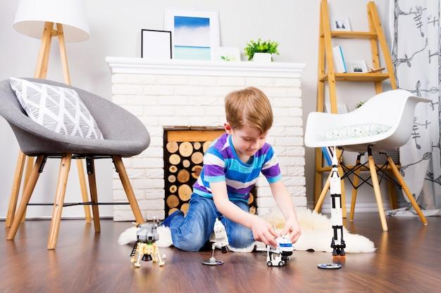 コスモスのおもちゃコンストラクターで遊ぶ若い子少年男性:木製の床に自宅で快適なインテリアでロケット、シャトル、ローバー、衛星、宇宙飛行士の人形