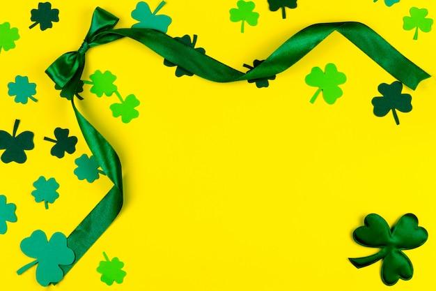 День святого патрика. зеленый дизайн изогнутой ленты, зеленый три лепестка клевера на желтом фоне