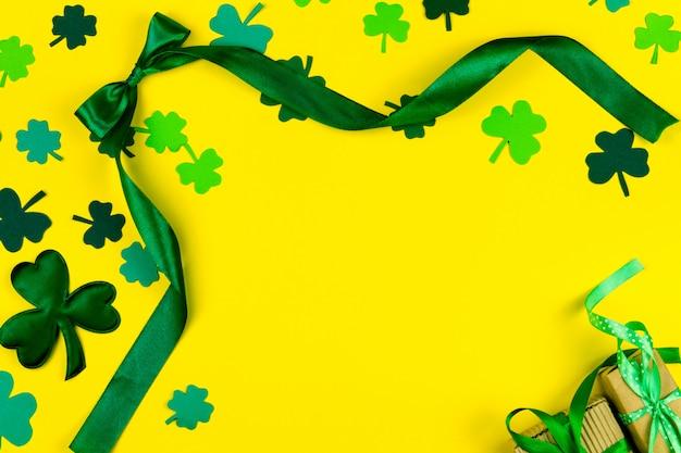 День святого патрика. зеленый дизайн изогнутой ленты, зеленый три лепестка клевера и подарочная коробка на желтом фоне