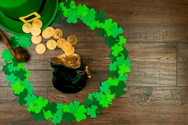 День святого патрика. мешочек с лепреконом с золотыми монетами, лежащими на деревянном фоне в форме круга из трех зеленых лепестков клевера