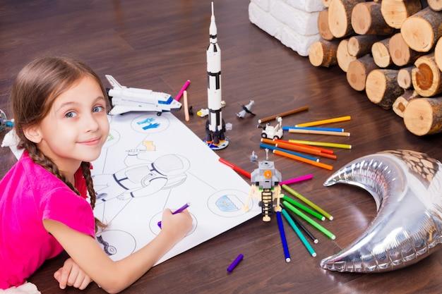 カラフルなペンで宇宙飛行士の衣装を塗装し、宇宙飛行士のコンストラクターのおもちゃでコスモスを夢見て若い子女の子女性