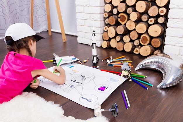 Девочка маленького ребенка, рисующая костюм космонавта красочными ручками и мечтающая о космосе с игрушками-космонавтами-конструкторами