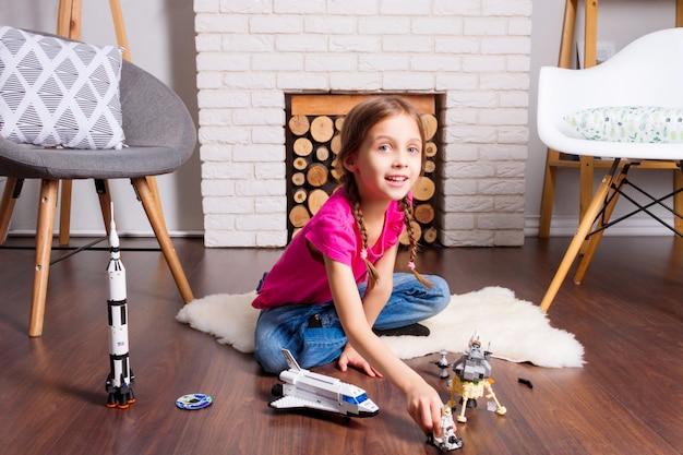 Девочка маленького ребенка, играющая с конструктором игрушек космоса: ракета, шаттл, ровер, спутник и кукла астронавта в уютном интерьере дома на деревянном полу