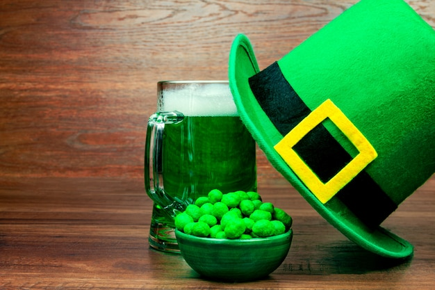 聖パトリックの日。ビールの緑のガラスのパイント、緑のスナッククッキーお菓子、木製のテーブルにレプラコーンの緑の帽子