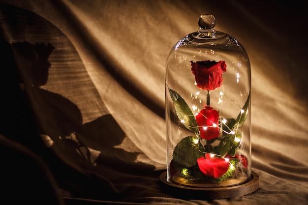 Цветок розы украшен в стеклянной посуде