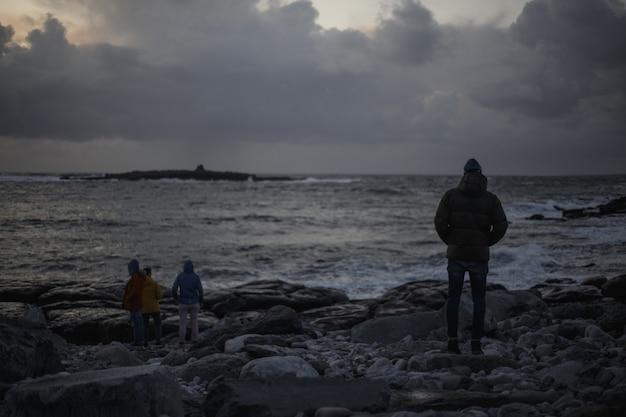 Люди на темном море с камнями и облаками