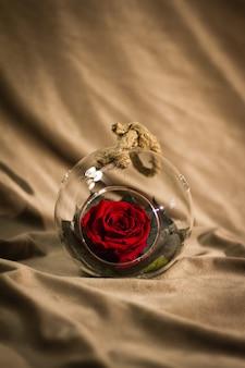 Цветок розы украшен в стеклянной посуде со шнуром