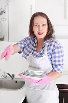 怒っている女性の台所で皿を洗う