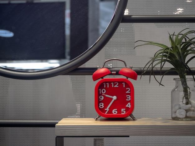 Красный ретро будильник на столе в ванной комнате.