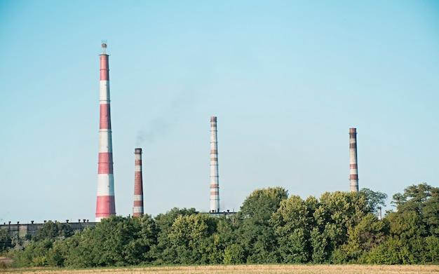 植物のパイプは森の上に上がります。産業景観。有害な環境生産。環境汚染。煙突からの煙。すすステーション。