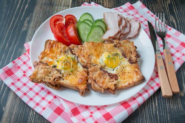 Жареный сэндвич с яйцом, овощами и беконом на темном деревянном фоне. вкусный завтрак. место для текста.