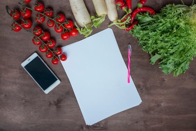新鮮な野菜の背景にキッチンテーブルの上のスマートフォン。食品の背景。テキストのための場所。背景メニューの表。健康的なバランスのとれた食べ物。