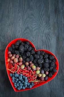 新鮮なフルーツブラックベリー、グーズベリー、赤スグリ、赤いハートボックスのブルーベリーのセット。バレンタインデーのコンセプト。暗い背景の木。テキスト用のスペース。