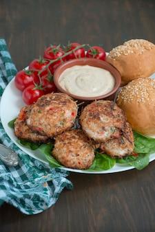 Котлеты из рубленого мяса с паприкой, помидорами и зеленью в миске на белом блюде с соусом. деревянный фон