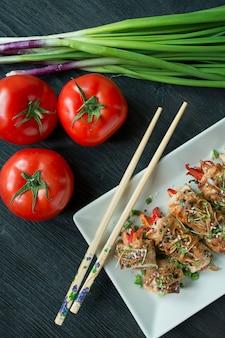 焼きたての鶏の胸肉は、ハーブ、にんじんのスライス、ピーマンと暗いまな板に巻きます。アジアンスタイル。健康的な食事のバランス。料理。暗い背景の木。