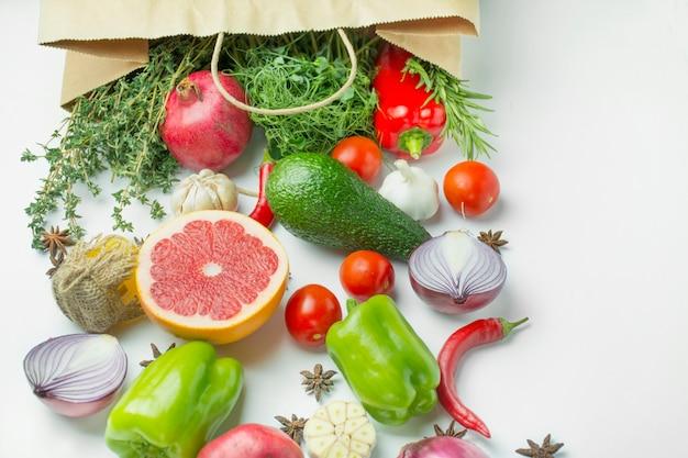 新鮮な野菜や食材を紙袋に入れます。新鮮な野菜や果物の白い背景の上の完全なパック。ダイエットやベジタリアン料理のコンセプト。テーブル背景メニュー。テキストのためのスペース。