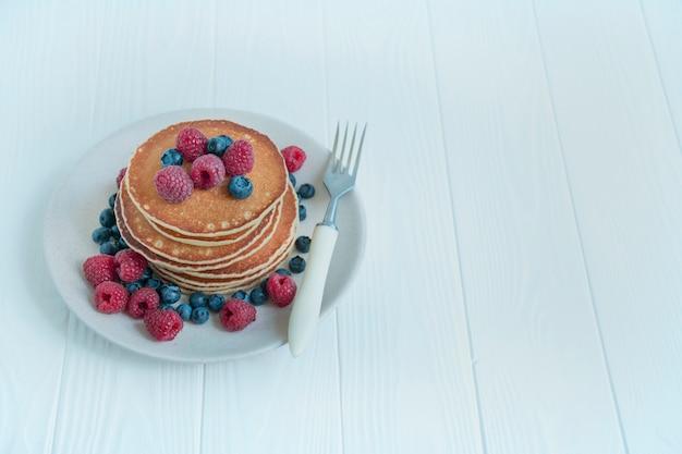 明るい背景に新鮮な果実のパンケーキ。フルーツのパンケーキ。伝統的なアメリカの朝食。自家製料理。コピースペース。健康的な食事のバランス。
