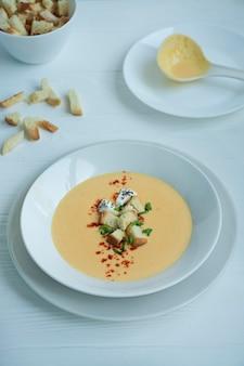 Сырный суп с крекерами, зеленью и сыром фета. крем-суп подается в белой тарелке. белый фон.