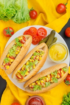 白い皿にソーセージ、トウモロコシ、レタスのホットドッグ。ファストフード。食品のカロリー量。上からの眺め。