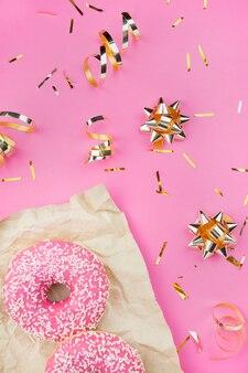 Пончики с розовой глазурью с золотым конфетти и бантами на розовом фоне. модный цвет и стиль. квартира лежала. копировать пространство идея блоггера.