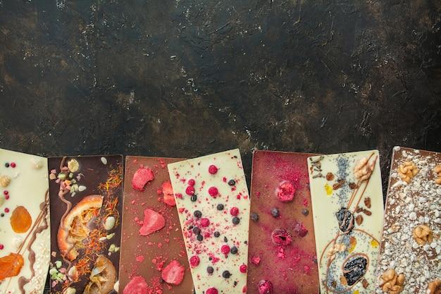 Ручной шоколад с ягодами, орехами, сухофруктами на темном фоне. черный и белый шоколад. плитка шоколада. шоколадный фон. рецепт. копировать пространство