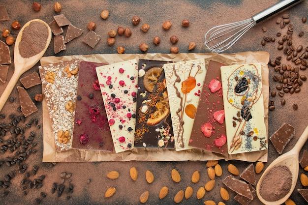 Ручной шоколад с ягодами, орехами, сухофруктами на темном фоне. черный и белый шоколад. плитка шоколада. крупный план. шоколадный фон. кулинарный фон.