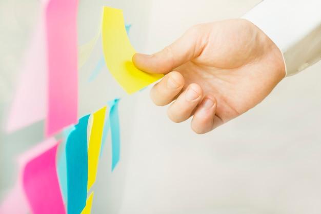 Мозговой штурм. мужская рука клеит разноцветные липкие заметки на доске - изображение. деловые заметки.