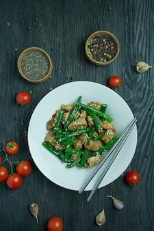Салат из зеленой фасоли и мяса, посыпанный кунжутом. порция горячего салата с зеленой фасолью. салат со спаржей. азиатская еда. темный деревянный фон.