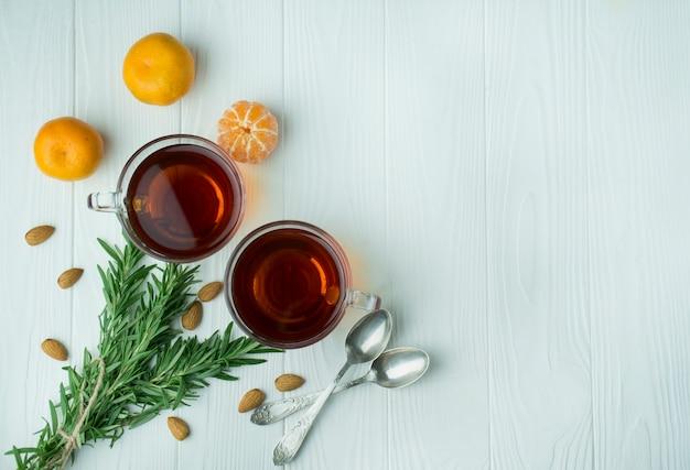 軽い木製の背景にガラスのコップでお茶。ローズマリー、みかんと紅茶。テキストのためのスペース。背景メニュー表。