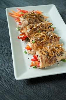 焼きたての鶏の胸肉は、ハーブ、にんじんのスライス、ピーマンを暗いまな板に巻きます。健康的な食事のバランス。料理。暗い木製のテーブル。