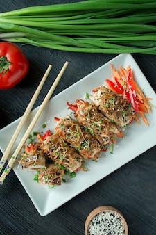 焼きたての鶏の胸肉は、ハーブ、にんじんのスライス、ピーマンを暗いまな板に巻きます。アジアンスタイル。健康的な食事のバランス。料理。暗い木製のテーブル。
