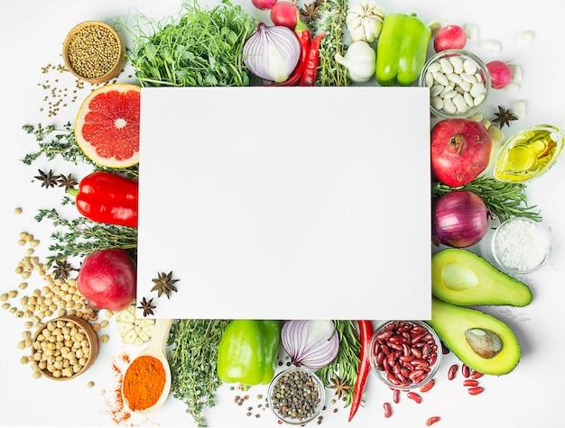 新鮮な野菜やヘルシーな食材。ダイエットやベジタリアン料理のコンセプト。調理台、ハーブ、塩、スパイス、オリーブオイル、白いテーブル。コピースペース。テーブルテーブルメニュー。
