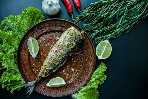 魚と野菜の調味料を皿に揚げサバ。暗い背景トップビュー。