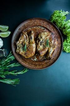 Жареная курица в гриле кастрюлю овощи на темном фоне.