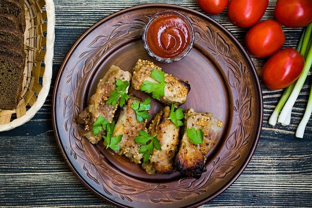Вкусные жареные ребрышки, заправленные медовым соусом, украшенные зеленью и овощами