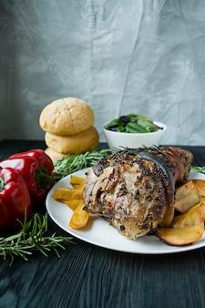 白いプレートにポテト添え豚肉のナックル炒め。