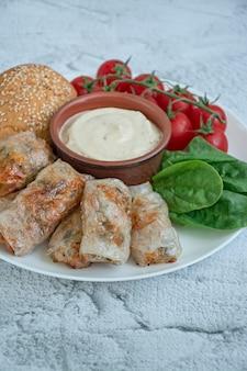 Спринг ролл с мясом и овощами подается на белом блюде с соусом
