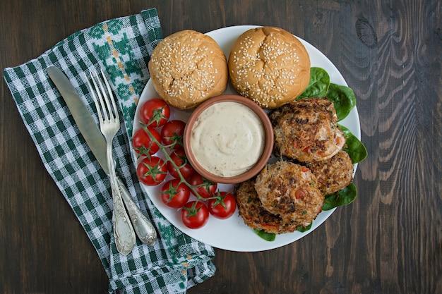 ソースと白い皿にボウルにパプリカ、トマト、ハーブ入りひき肉のカツレツ