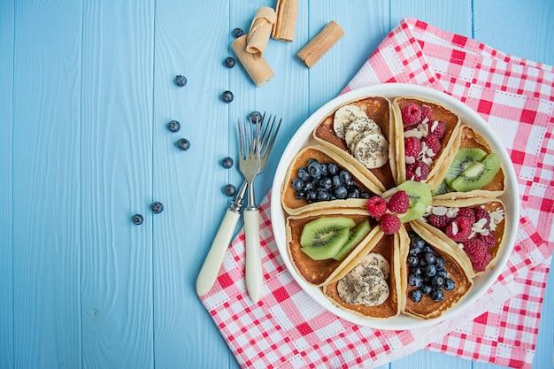 青い木製のテーブルに新鮮なベリーと古典的なアメリカのパンケーキ。フルーツのパンケーキ。