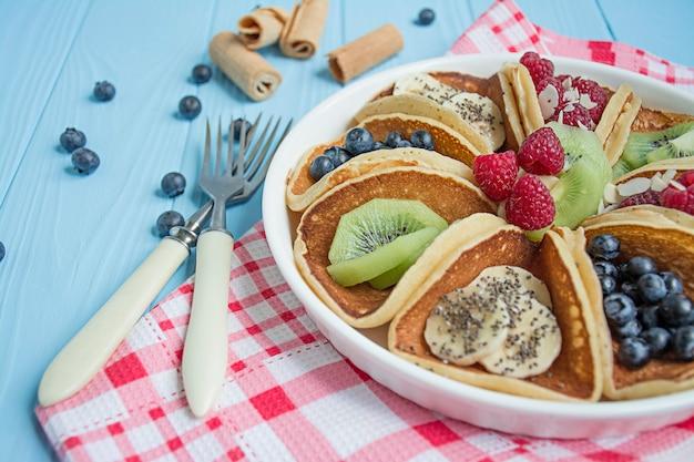 青い木製のテーブルに新鮮なベリーと古典的なアメリカのパンケーキ。フルーツのパンケーキ。夏の自家製朝食。